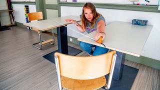 Teacher measures distance between desks