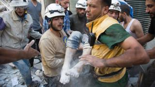 July 23, 2016 shows Syrian civil defence volunteers, known as the White Helmets, carrying a body after digging it out from under the rubble of a building following a reported airstrike