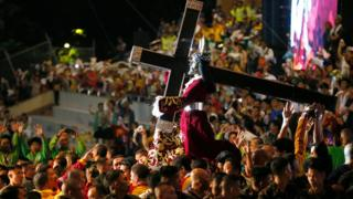 The Black Nazarene and cross on a carriage, surrounded by thousands of devotees. 9 January 2017, Manila, Philippines.