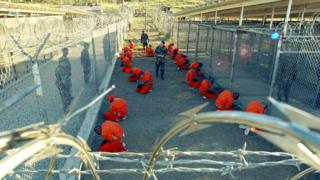US Military Police guard Taliban and al-Qaeda detainees in orange jumpsuits January 11, 2002
