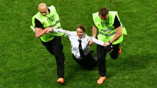Una joven es llevada a rastras por guardias de seguridad tras invadir el campo durante la final del Mundial en Rusia.