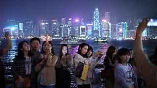 People taking selfies by Hong Kong harbour.
