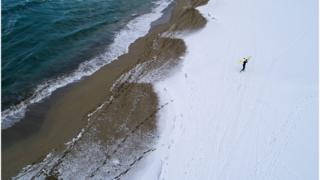 Мужчина идет с доской по снегу