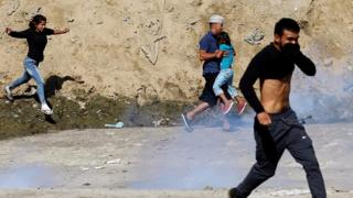 Migrants and children covering mouths with tear gas cloud behind