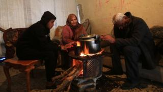 Etadal Abu Oda prepares food with her husband and son at their damaged house in Beit Hanoun in the northern Gaza Strip (26 January 2016)