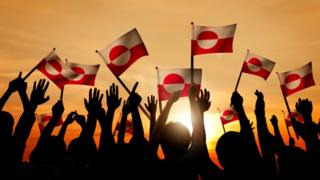 People waving Greenland flag