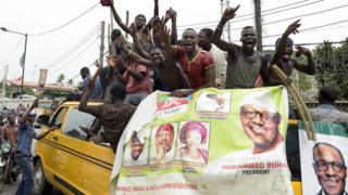 Supporters of newly-elected Nigerian President Muhammadu Buhari sit on top of a bus as they celebrate the victory their candidate in Lagos on April 1