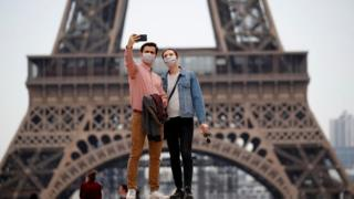 People taking a selfie with facemasks in front of the Eiffel Tower, Paris.