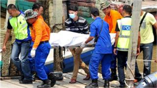 Rescuers carry a body recovered from a capsized boat believed to be carrying illegal migrants, at a jetty in Hutan Melintang
