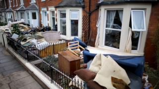Water-damaged possessions sit outside a flooded home in Carlisle after flooding created by Storm Desmond
