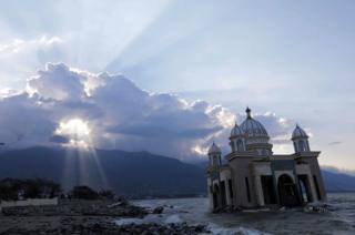 A mosque is seen on a beach amid strewn debris