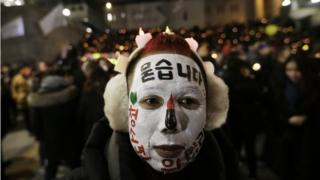 A protester with his face painted attends a candle light vigil calling for impeached President Park Geun-hye to step down in Seoul, South Korea, on 31 December 2016