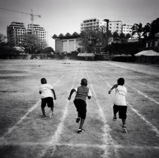 Three boys run on a school track