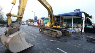 A burnt-out digger in front of the damaged filling station