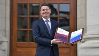 Paschal Donohoe holds a folder containing his Irish budget document