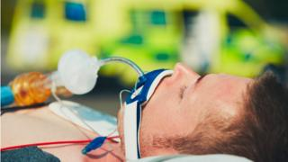 Patient on stretcher beside ambulance