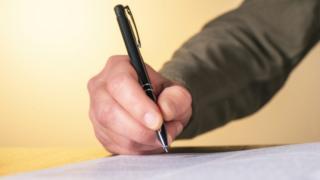 Un hombre escribe una carta.