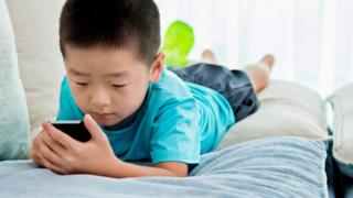 Boy playing on a smartphone.