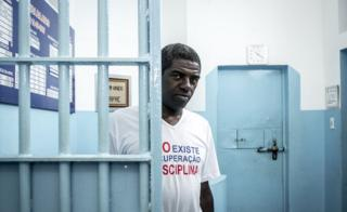 A man stands behind bars in a Brazilian jail