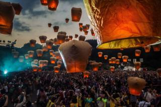 A crowed releases lanterns with flames into the air