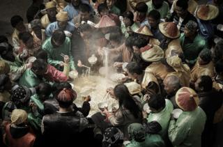 People stand around a giant cauldron eating noodles