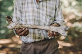 Ramiz holds a human bone.