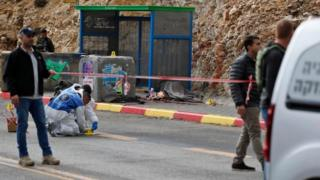 Israeli forces and forensic inspect the site of a drive-by shooting attack outside the West Bank settlement of Givat Asaf, northeast of Ramallah, on 13 December 2018.