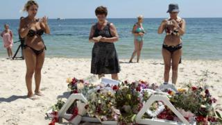 Tourists photograph flowers left at the site of Friday's attack in Tunisia