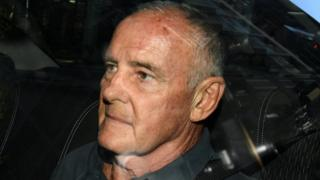 Chris Dawson arrives at Sydney police station in a police car