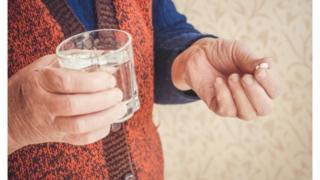 пожилая женщина со стаканом воды и таблеткой