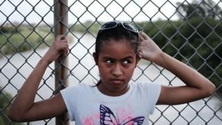 A girl waits on a bridge at the US-Mexico border