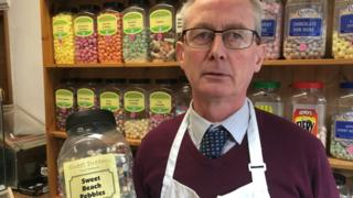 Nigel Parrott in his shop, with jars of sweets
