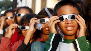 Children watch the eclipse through special protective glasses.
