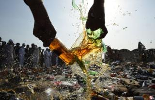 A Pakistani customs official smashes bottles of liquor.