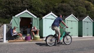 Rob and Sally Underhill sit outside their beach hut as they enjoy the hot weather at Bournemouth beach in Dorset on 20 May
