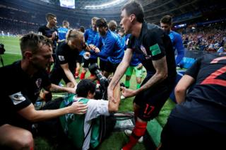 Croatia's Mario Mandzukic helps an AFP photographer Yuri Cortez to his feet after celebrating scoring their second goal