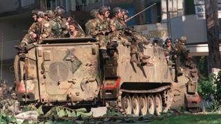 US soldiers sit on top of armoured vehicles in a street of Panama City during Operation Just Cause on 23 December, 1989