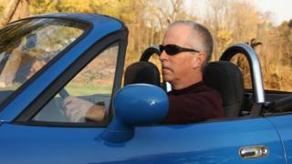 Middle aged man in a sportscar