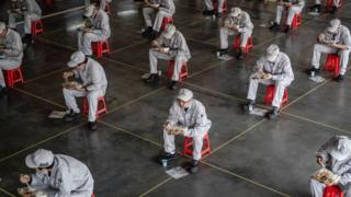 Workers eating during lunch break at the Dongfeng Honda plant in Wuhan in China's central Hubei province