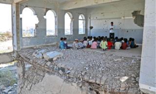 Yemeni children attend class in a badly damaged school building