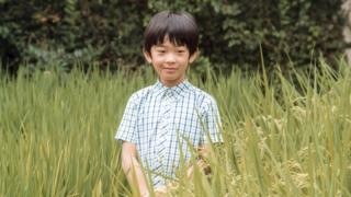 Prince Hisahito poses on a paddy field at the Akishino-no-miya residence in Tokyo