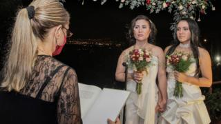 Same-sex newlyweds stand before a lawyer during their wedding