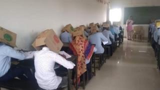 الطلاب يرتدون صناديق أثناء تأدية امتحان
