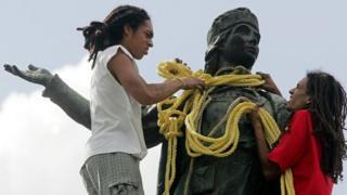 Dos jóvenes ponen una cuerda sobre el cuello de la estatua