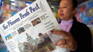"A Cambodian vendor reads the Phnom Penh Post newspaper at her newstand in Phnom Penh on May 7, 2018. The newspaper hailed as Cambodia""s last independent English daily has been sold to a Malaysian investor with apparent business links to premier Hun Sen, rattling a journalist community that has been battered by the strongman ahead of elections."