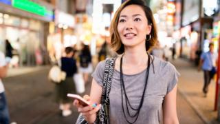Woman walking in street with smartphone