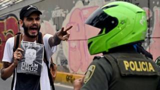 in_pictures A demonstrator holding a poster of the late Dilan Cruz shouts at riot police during a march against the government of Colombian President Ivan Duque during a national strike in Cali on November 27, 2019