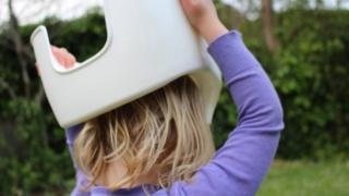 Child with a potty on its head