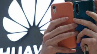The Huawei logo is seen behind a man's hands, holding two Huawei phones