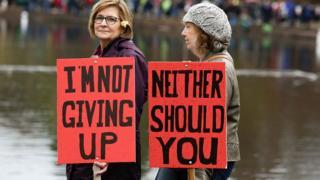 Dos mujeres en Seattle sostienen carteles de protesta en una de las residencias de Trump